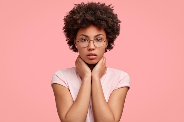 Headshot di bella donna afroamericana seria mantiene entrambe le mani sul collo