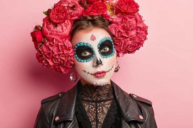 Headshot of serious beautiful woman wears sugar skull makeup, celebrates mexican day of dead, wears big earrings, flower wreath, black leather jacket.