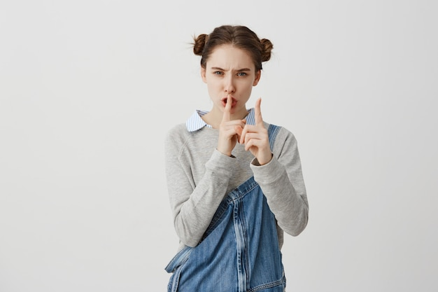 Headshot of serious caucasian woman holding index finger on lips. strict housewife wearing jeans jumpsuit asking to be mute because her children sleeping. silence concept