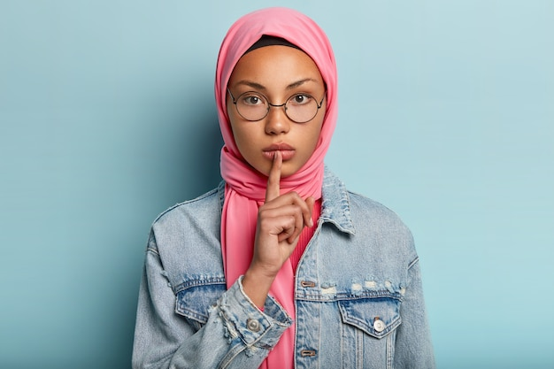 Headshot of serious female in pink scarf, denim coat, keeps fore finger over lips, asks not make noise, makes hush gesture, has islamic believes, wears round optical glasses