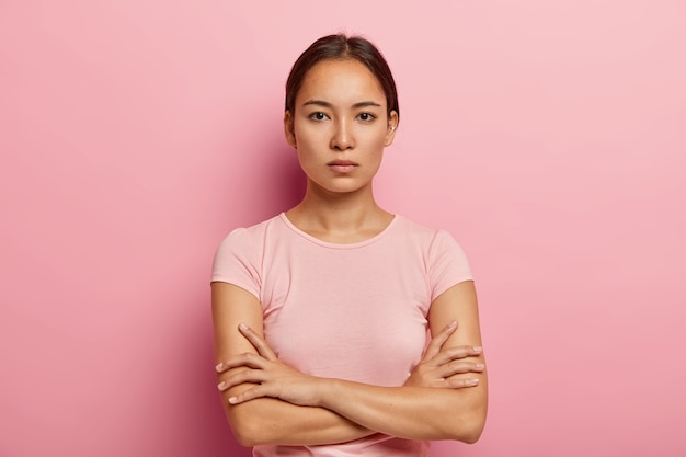 Headshot of serious korean woman looks with calm face expression, keeps arms folded, has healthy fresh skin, wears rosy t shirt, stands indoor. beautiful asian girl has confident gaze