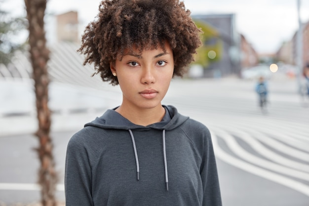 Headshot of serious thoughtful female teenager dressed in casual sweatshirt, goes in for sport on street