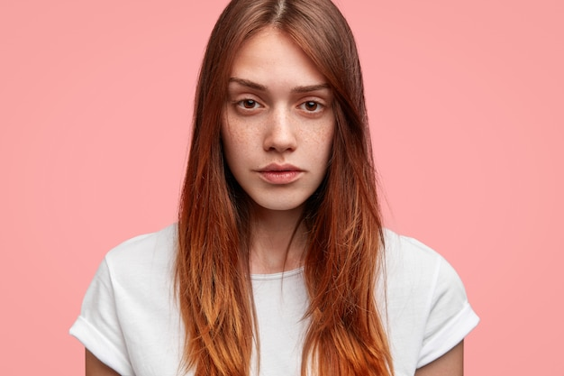 Headshot of serious thoughtful freckled female looks directly at camera, has long hair, wears casual white t shirt, poses against pink studio background.
