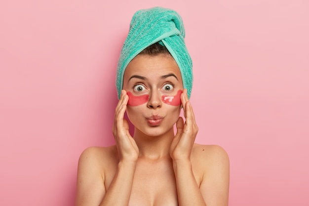 Headshot of shocked bare shoulders woman has natural beauty, reduces wrinkles under eyes, applies collagen patches, has wrapped towel on head