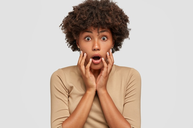 Headshot of shocked beautiful black woman opens mouth widely, keeps both hands on cheeks