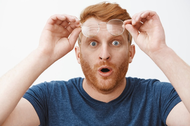Headshot of shocked and impressed overwhelmed redhead guy with beard, taking off glasses and holding rim on forehead, folding lips and staring with popped eyes at impressive and curious thing