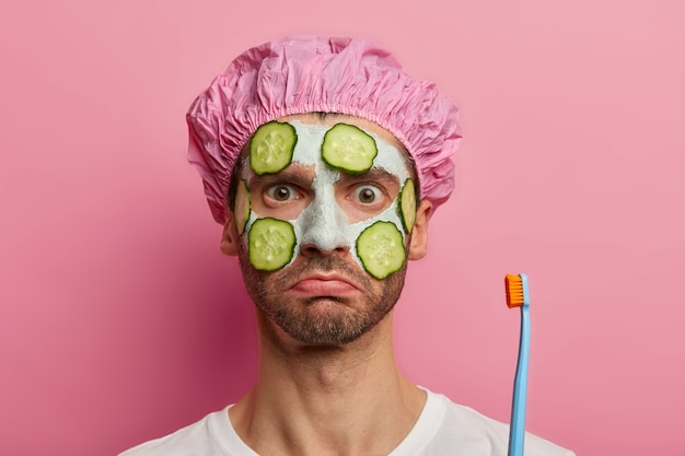 Headshot of shocked man cleanses facial skin, holds toothbrush, shower cap, ready for cleaning teeth, has serious strict look, models against pink space