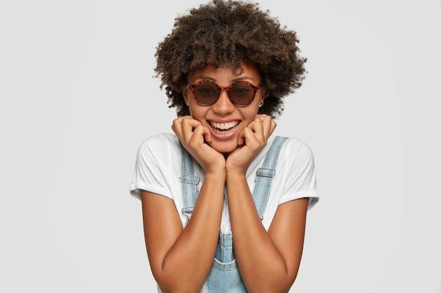 Headshot di sorridente signora africana soddisfatta, ha i capelli folti, felice espressione