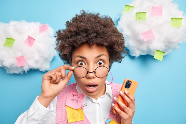 Headshot of startled young female teacher reacts on shocking information keeps hand on rim of spectacles uses modern smartphone for texting writes tasks to do on colorful stickers