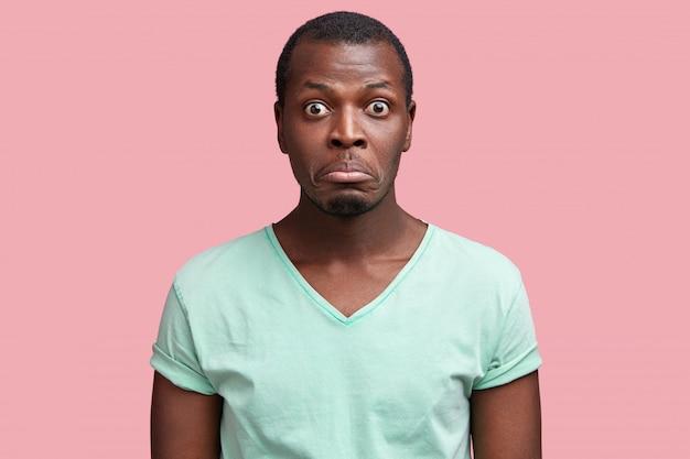 Il primo piano del volto di un maschio afroamericano, stordito e dispiaciuto, curva le labbra mentre sente qualcosa di inaspettato, esprime sorpresa, si veste casualmente, si acciglia.