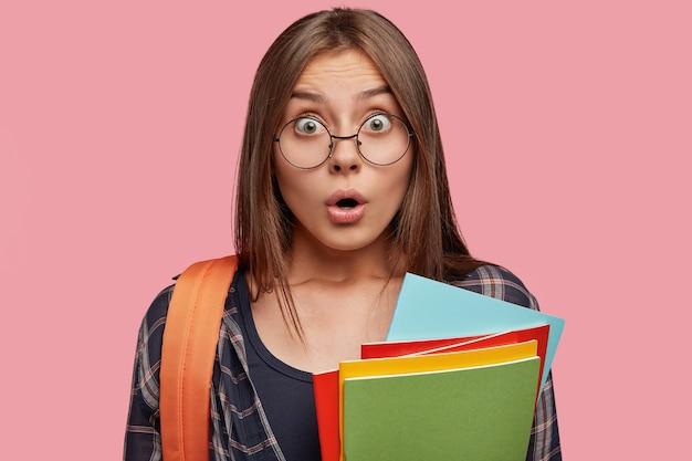 Primo piano del volto di studente sbalordito in posa contro il muro rosa con gli occhiali