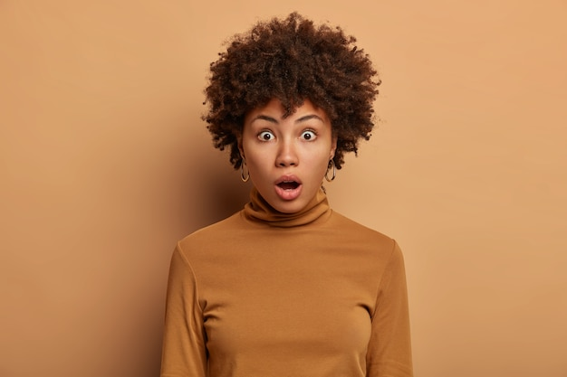Headshot of stunned woman with afro hair, wonders something, gasps from excitement, keeps mouth opened, dressed in casual poloneck, isolated over beige wall. no way. unlikely to be true