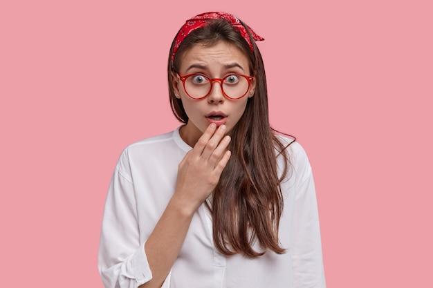 Primo piano del volto di una giovane donna disperata e stupefatta tiene la mano sulla mascella caduta, indossa una fascia rossa e occhiali da vista