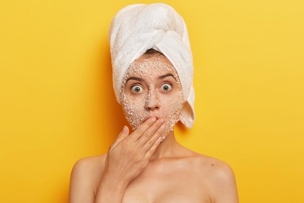 Headshot of stupefied young woman with natural scrub mask on face, gasps from fear, covers mouth with palm, reduces pimples stands shirtless exfoliates blackheads stares with popped out eyes