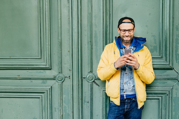 Headshot of stylish man with beard and broad forehead in yellow anorak, jeans and cap in big glasses holding cell phone