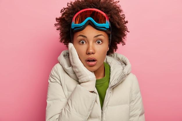 Primo piano del volto di una donna afroamericana sorpresa che tiene la mano sulla guancia, guarda con paura, indossa occhiali da sci e capispalla