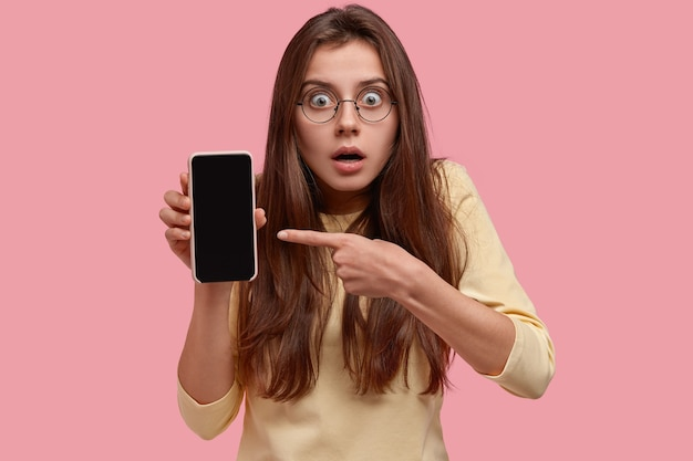Headshot of surprised beautiful caucasian woman has scared expression, points at mobile phone