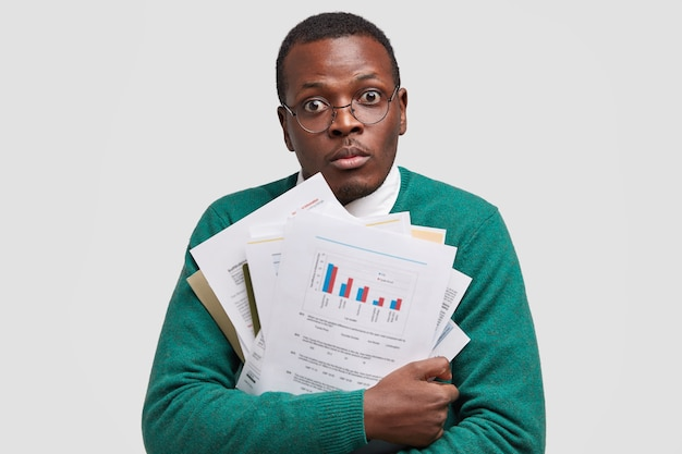 Headshot of surprised businessman carries paper documents with graphics, busy working, makes project has dark healthy skin, isolated over white space