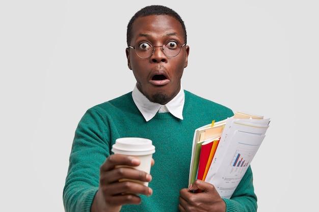 Colpo alla testa dell'uomo sorpreso dalla pelle scura tiene il caffè da asporto, trasporta documenti, sorpreso di sentire notizie scioccanti