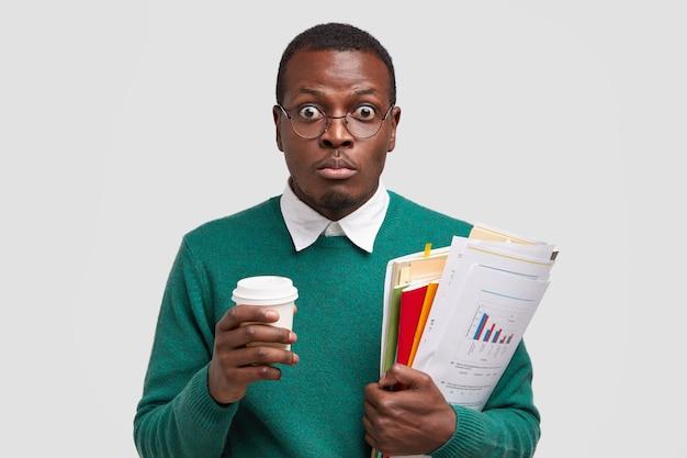Headshot of surprised dark skinned man owns entreprise, drinks takeaway coffee