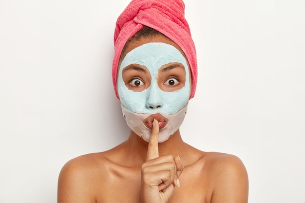 Headshot of surprised young female makes hush hand sign, tells beauty treatment, looks with bugged eyes, applies clay facial mask, silicone patch near lips, has mysterious expression, tells be qiet