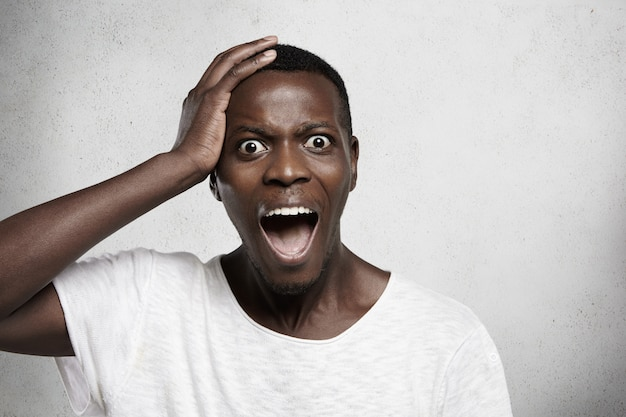 Headshot of terrified young african employee in white t-shirt holding hand on his head and screaming with horrified look, opening mouth widely. black male feeling scared or stressed.
