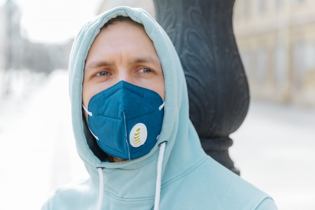 Headshot of thoughtful young man wears hood and respiratory mask, walks on street, protects from coronavirus, thinks about dangerous disease, being in danger. spreding covid-19 around world.