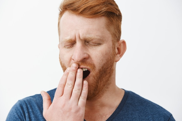 Headshot of tired attractive male entrepreneur with red hair and beard, yawning with closed eyes, covering opened mouth with palm, feeling tired, sleepy after taking nap or waking up early in morning