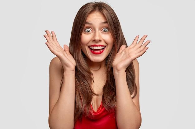 Headshot di donna con espressione allegra mantiene i palmi vicino al viso, reagisce a notizie positive, non posso credere nel successo