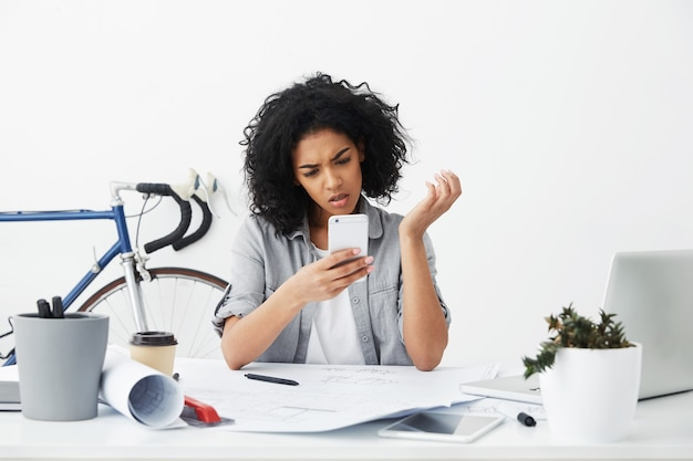 Headshot of worried or frustrated young mixed race woman architect reading urgent text message