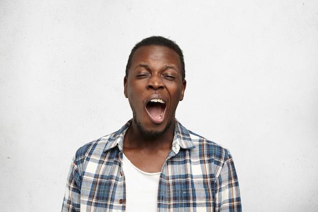 Headshot of young bored black man, yawning isolated on light background.