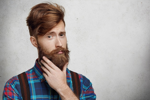 Headshot of young fashionable caucasian man with stylish haircut, touching his perfect thick fuzzy beard while thinking of something important, standing against blank concrete wall