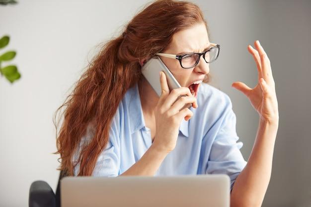 Primo piano del volto di un giovane capo femminile che grida con rabbia sul telefono cellulare mentre è seduto alla scrivania