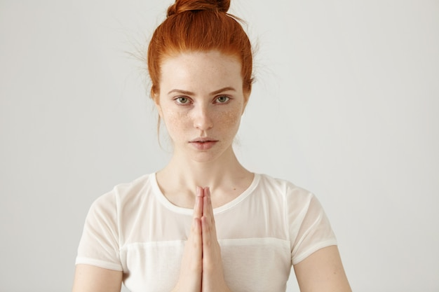 Headshot of young redhead freckled caucasian woman posing with hands pressed together in namaste while practicing yoga at white wall in the morning, having concentrated calm expression on her face