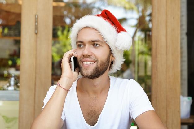 Primo piano del volto di giovane uomo con la barba lunga vestito con t-shirt bianca e cappello rosso di babbo natale che sembra felice mentre parla al cellulare con la sua ragazza, ascoltando le sue calorose congratulazioni per il natale