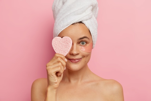 Headshot of young woman applies patches under eyes for having fresh skin and young outlook, covers eye with cosmetic sponge, wears white towel on head after taking shower, takes care of beauty