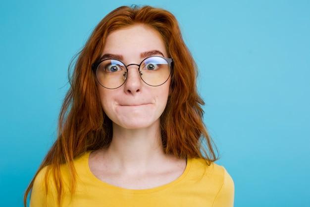 Headshot портрет счастливый рыжий рыжий волосы девушка с смешным лицом, глядя на камеру. пастель синий фон. копирование пространства.