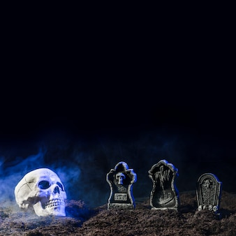 Headstones and skull in fog on soil