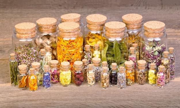 古い木製のテーブルの上の薬草のためのボトルのハーブを癒す