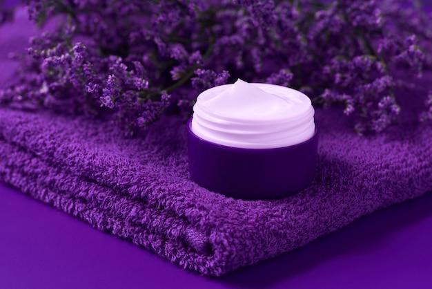 치유의 밤 허브 화장품 크림, 위생적인 피부 관리 제품 또는 나무 테이블에 수건이 있는 플라스틱 병에 든 편안한 메이크업 마스크.