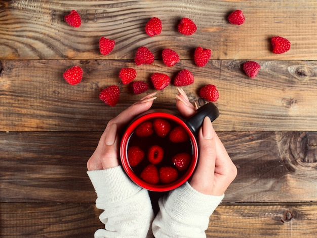 Healing tea with raspberries and berries on the table. a cup in the hands of a girl. combating colds in winter by natural methods.