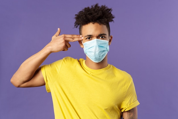 Healtcare and medicine concept. close-up portrait of serious hispanic guy in medical mask, showing gun near head as if sick and tired of people not avoid social contact, purple background