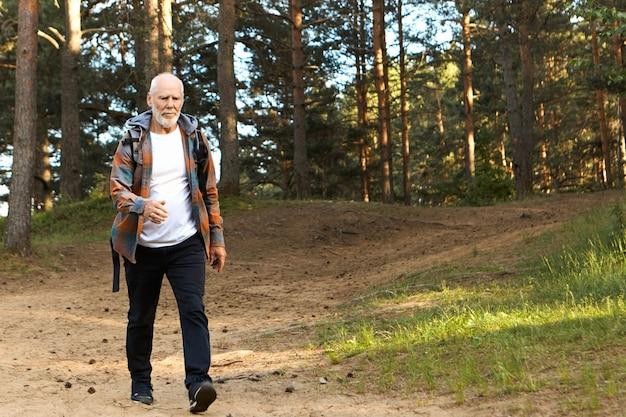 Concetto di salute, attività, benessere, età e persone. uomo europeo barbuto attivo autodeterminato sulla sessantina che cammina veloce durante il trekking nella foresta di montagna, con uno sguardo sicuro e concentrato