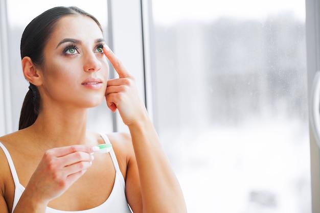 건강과 아름다움. 녹색 눈을 가진 아름 다운 소녀 손가락에 콘택트 렌즈를 보유하고있다. 눈 관리. 좋은 비전 신선한 전망. 높은 해상도