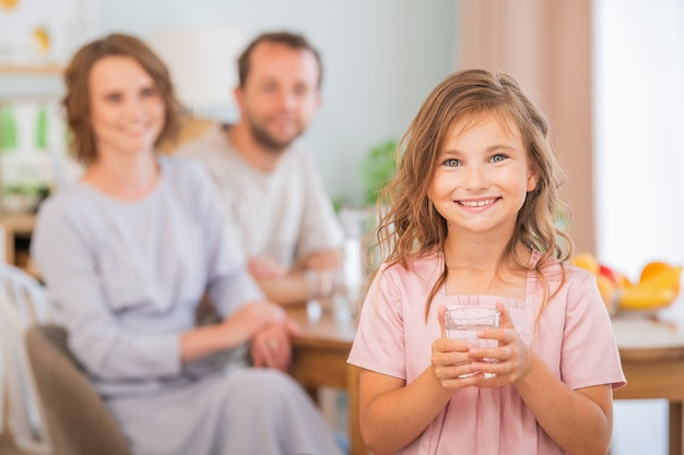健康と美容のコンセプト-水を一杯持っている笑顔の少女。バックグラウンドで幸せな親。