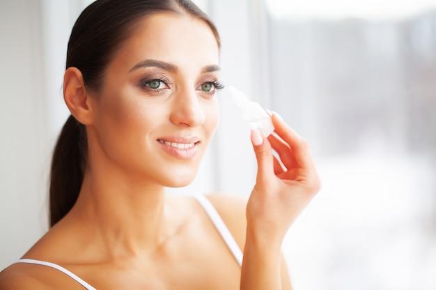 건강과 아름다움. 눈 관리. 들고 아름 다운 젊은 여자는 눈을 삭제합니다.