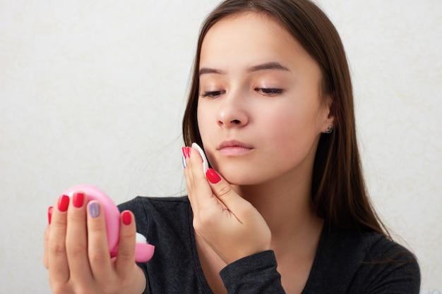 Здоровье и красота. уход за кожей лица. молодая девушка трет лицо тонизирующим питательным лосьоном.