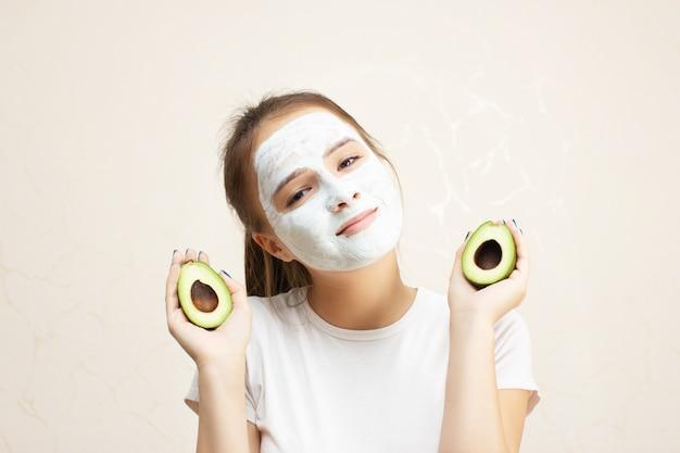 건강과 아름다움. 얼굴 피부 관리. 어린 소녀는 보습 클렌징 페이스 마스크를 만든다.