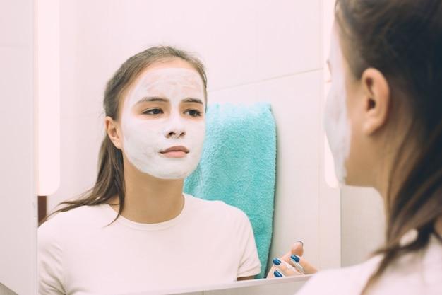 美容と健康。フェイシャルスキンケア。若い女の子が保湿クレンジングフェイスマスクを作ります