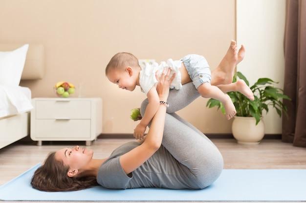 健康とフィットのコンセプト。彼女の小さな子供の息子と一緒に国内の部屋でフィットネス運動をしている若い美しい妊娠中のアジアの女性。フィットネスの母性と母性